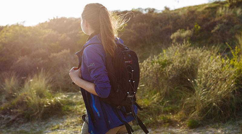Vrouw met rugzak aan het wandelen in duinen