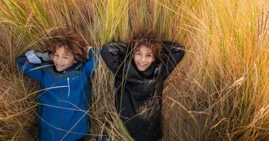 Twee jongens liggen in duinen